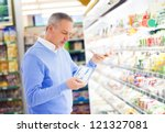 Man comparing products at the supermarket - stock photo