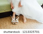 the bride puts on white shoes... | Shutterstock . vector #1213325701