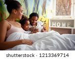 happy mother lying in a bed... | Shutterstock . vector #1213369714