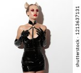 Small photo of Beautiful dominant blonde devil demon vamp mistress bdsm girl with hair horns in glamour latex skirt, corset, collar and bdsm black leather fetish harness posing on white background