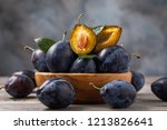 Small photo of Full plate of ripe prune fruits on a wooden table, close-up