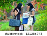 laughing women in autumn park with shopping packages - stock photo