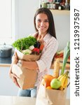 young woman holding grocery... | Shutterstock . vector #1213937587