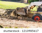 small bulldozer digging in yard ... | Shutterstock . vector #1213985617