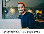 Small photo of Portrait of cheerful caucasian man in trendy bennie satisfied with online language courses using netbook for studying, happy bearded hipster looking at camera satisfied with wifi for remote work