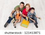 Family with two kids ready to pait their home - sitting on the protection foil, top view - stock photo