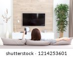 young woman watching tv in the... | Shutterstock . vector #1214253601