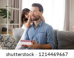 Small photo of Head shot diverse family at home little daughter cover dad eyes with hands prepare for him a gift. Man with closed eyes feels excited hold surprise box received from loving kid. father day concept