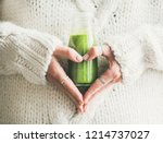 Small photo of Winter seasonal smoothie drink detox. Female in woolen sweater holding bottle of green smoothie or juice making heart shape with her hands. Clean eating, weight loss, healthy dieting food concept
