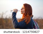 young redhead girl drinks water ... | Shutterstock . vector #1214750827