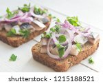 Stock photo two open sandwiches with herring red onion and parsley 1215188521
