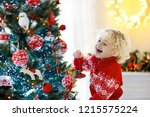 child decorating christmas tree ... | Shutterstock . vector #1215575224