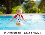 child playing in swimming pool. ... | Shutterstock . vector #1215575227