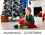 child opening present at... | Shutterstock . vector #1215576844