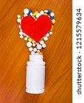 red heart shape with a pills on ... | Shutterstock . vector #1215579634