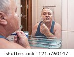 mature man shaves in bathroom... | Shutterstock . vector #1215760147