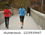 Small photo of 2 young women walk briskly over a bridge in the Fall