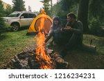 couple sitting near camp fire...   Shutterstock . vector #1216234231