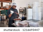 african worker standing at a... | Shutterstock . vector #1216693447