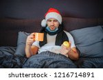 sick young man sits on bed. he... | Shutterstock . vector #1216714891