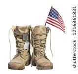 Old military combat boots with the American flag and dog tags, isolated on white background. Memorial Day or Veterans day concept.