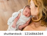 newborn in arms looks at his... | Shutterstock . vector #1216866364