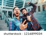 Small photo of Two friends showing sincere emotions of joy about victory in online lottery. Men being happy winning a bet in online sport gambling application with football stadium on the background.