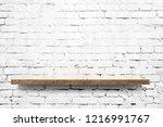 wooden shelf over white brick... | Shutterstock . vector #1216991767
