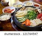 Boiled Korean food consisting of meat, ginseng, mushrooms and vegetables. There are rice, dipping sauce and some pickled bean sprouts on a wooden table.