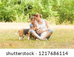Stock photo adorable couple daughter and mom sitting on a grass with their pets 1217686114