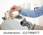 Female teller putting money into currency counting machine at cash department, closeup - stock photo