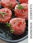 Fresh meat with spices and rosemary on a grill pan. - stock photo