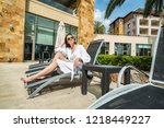 woman on a lounger by the pool | Shutterstock . vector #1218449227