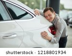 Small photo of Close up of adult content caucasian man being completely satisfied with his new car, hugging it with eyes closed and leaning on car bonnet