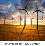 golden wheat with wind turbines in the sunset - stock photo
