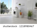 Stock photo laundry room interior with washing machine near wall 1218980467