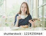 girl sits at table with coffee... | Shutterstock . vector #1219250464