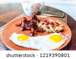Small photo of Large breakfast brunch plate closeup with fried eggs, hash browns shredded potatoes, ketchup, sausage tako octopus, coffee cup, smartphone phone
