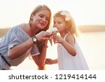 mom with her daughter shares... | Shutterstock . vector #1219414144