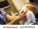 barber puts on man face hot... | Shutterstock . vector #1219594924