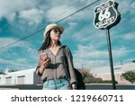 tourism in america concept. happy teenage girl with sunglasses standing over route 66 background. young lady using online map app on smartphone app finding the right direction on the trip.