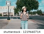 young lady traveler joyfully looking at the blue sky. asian tourist travel in usa and visiting the famous landmark. cheerful standing on the empty road carrying backpack.