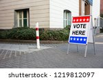 Small photo of Polling Place Vote Here Sign On White Board Near House