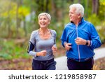 Smiling senior couple jogging...
