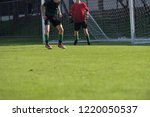 Small photo of Football match in Boys' Under 18 years school soccer tournament. Defender and goal keeper are in action of defending mode.