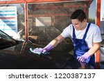 worker cleaning automobile with ... | Shutterstock . vector #1220387137