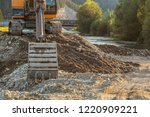 small yellow excavator at pile... | Shutterstock . vector #1220909221