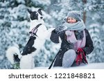 Stock photo woman playing with dog in snowy forest enjoying the weather running and jumping happy pet girl 1221848821