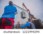 Two Male Workers Lifting A Big...