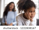 Small photo of Offended African American preschooler girl looking in distance, holding head in hands, talking mother on background, family conflict, child punishment, complicated relationships with parent, close up